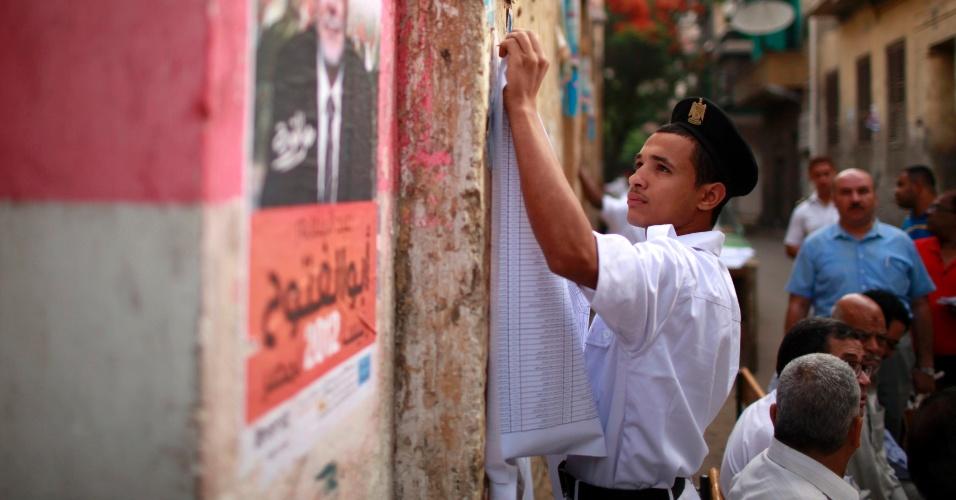23.mai.2012 - Policial egípcio fixa lista com nomes de eleitores do lado de fora de sessão eleitoral no Cairo (Egito)