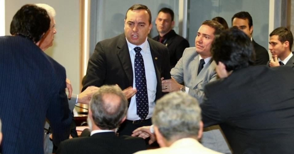 """24.mai.2012 - Os deputados Fernando Francischini (PSDB-PR), na imagem em pé, e Dr. Rosinha (PT-PR) --sentado de costas-- batem boca durante reunião da CPI do Cachoeira. A discussão começou depois de o tucano ironizar a postura do relator da CPI, Odair Cunha (PT-MG), e chamá-lo de """"tchuchuca"""" e """"tigrão"""""""