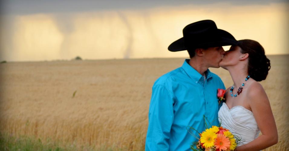 Os noivos Caleb e Candra Pence posam para a foto do casamento com um tornado como cenário, em Harper County, Kansas