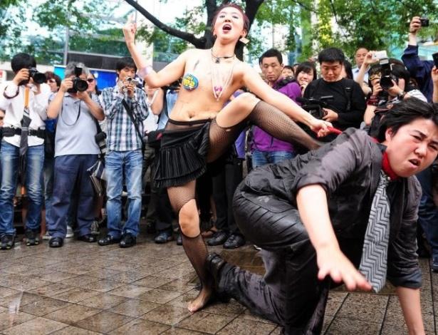 16.jun.2011 - Mulher de topless faz performance com um homem durante a Marcha das Vadias, em Seul, na Coreia do Sul. O movimento reivindica que as mulheres possam se vestir e agir como quiserem, sem serem reprimidas por sua sexualidade