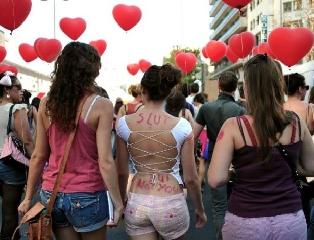 1º.out.2011- Manifestante usa as costas para escrever mensagens contra a violência sexual durante a Marcha das Vadias (SlutWalk, em inglês), em Paris, na França