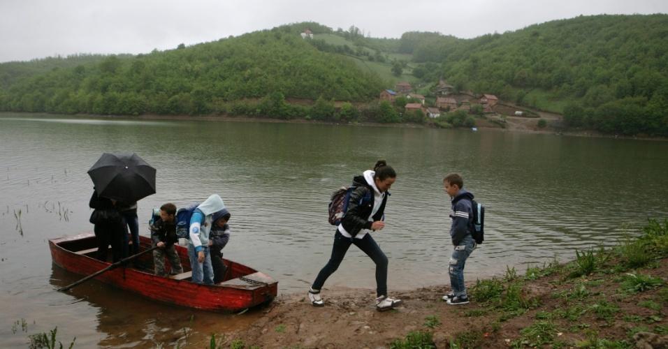 25.mai.2012 - Alunos atravessam o lago Batllava em barco para ir à escola no vilarejo de Orllane, no Kosovo. O lago artificial abastece a cidade de Pristina