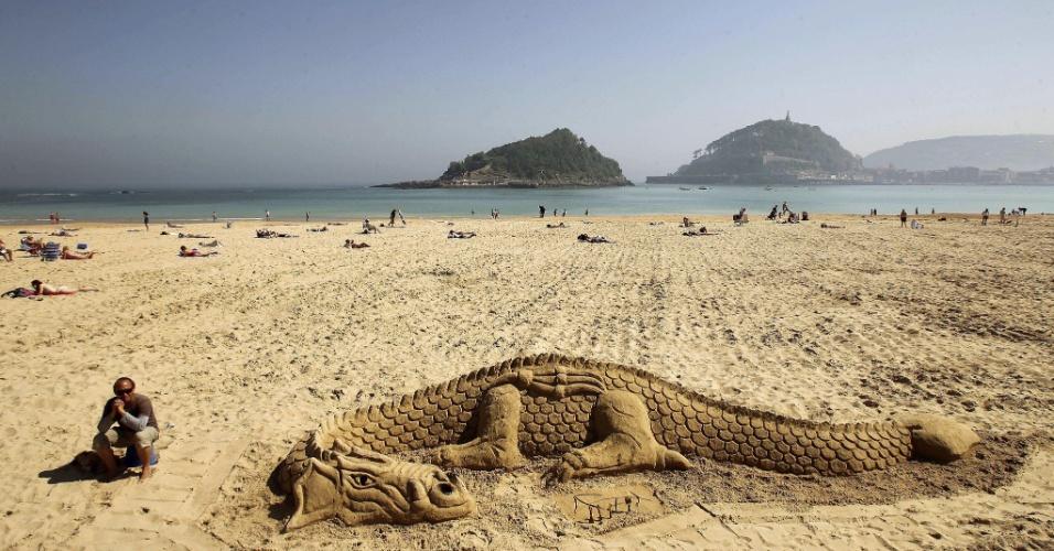 25.mai.2012 - Artista anônimo descansa ao lado da escultura de um dragão feita nas areias da praia de Ondarreta, em San Sebastian (Espanha)