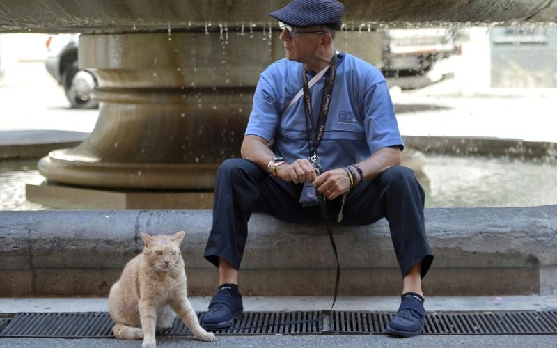 25.mai.2012 - Homem senta-se nesta sexta-feira (25) em fonte ao lado de hato em Roma, na Itália