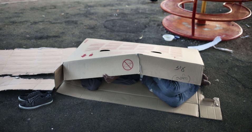 25.mai.2012 - Imigrante africano dorme dentro de caixa em parque infantil  em Tel Aviv, Israel