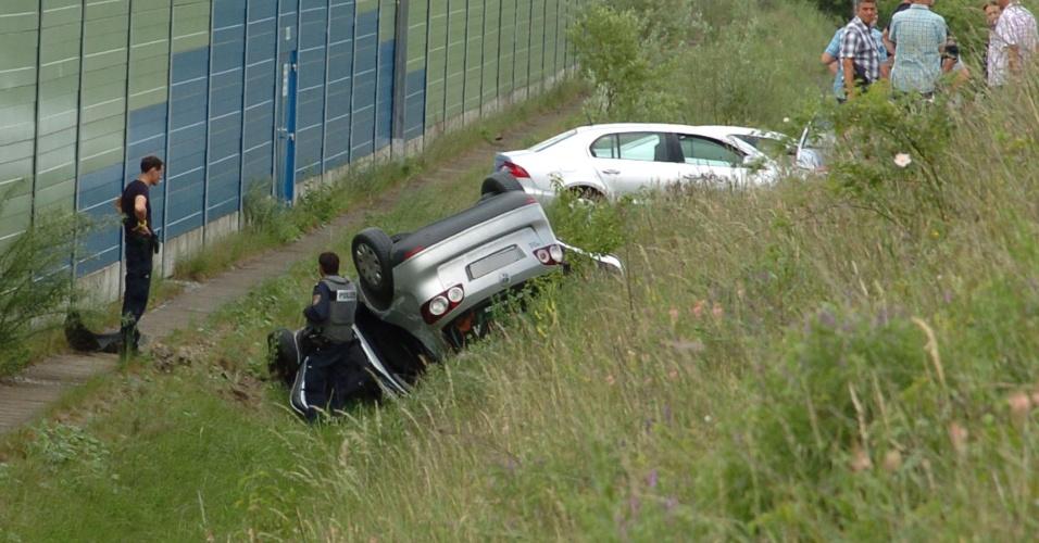 25.mai.2012 - Policiais observam nesta sexta-feira (25) um carro de ponta-cabeça em Sankt Poelten, a oeste de Viena, na Áustria. O motorista do veículo, de 37 anos, atirou no filho de 7 anos e pouco depois, após ser perseguido pela polícia, o homem foi encontrado morto em seu carro