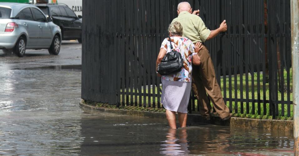 25.mai.2012 - Senhora tenta atravessar rua alagada de Recife (PE), após forte chuva que atingiu a capital pernambucana nesta sexta-feira