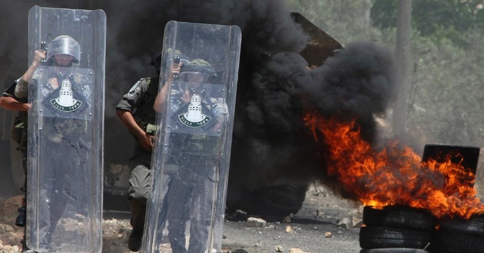 25.mai.2012 - Soldados israelenses usando máscaras de gás passam por fumaça preta provinda de pneus queimados durante confrontos com manifestantes palestinos nesta sexta-feira (25) na vila de Kfar Qaddum, em Israel