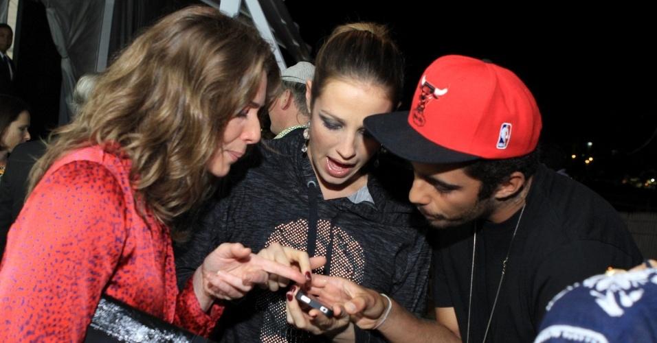 Ao lado do marido, Pedro Scooby, Luana Piovani mostra as fotos do filho, Dom, para a atriz Letícia Spiller no Fashion Rio 2013 (24/5/12)