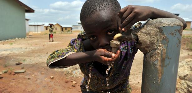 """Menino bebe água da torneira em uma das """"cidades novas"""" construídas por companhias de mineração na região de Koidu, em Serra Leoa"""