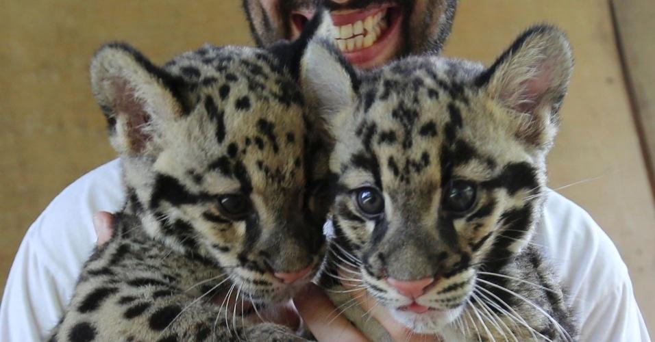 27.mai.2012 - O veterinário espanhol Fernando Najera, diretor de um centro pioneiro na reprodução de leopardos em cativeiros apresenta os filhotes Lek (pequeno) e Yai (grande), no zoológico de Chonburi, na Tailândia