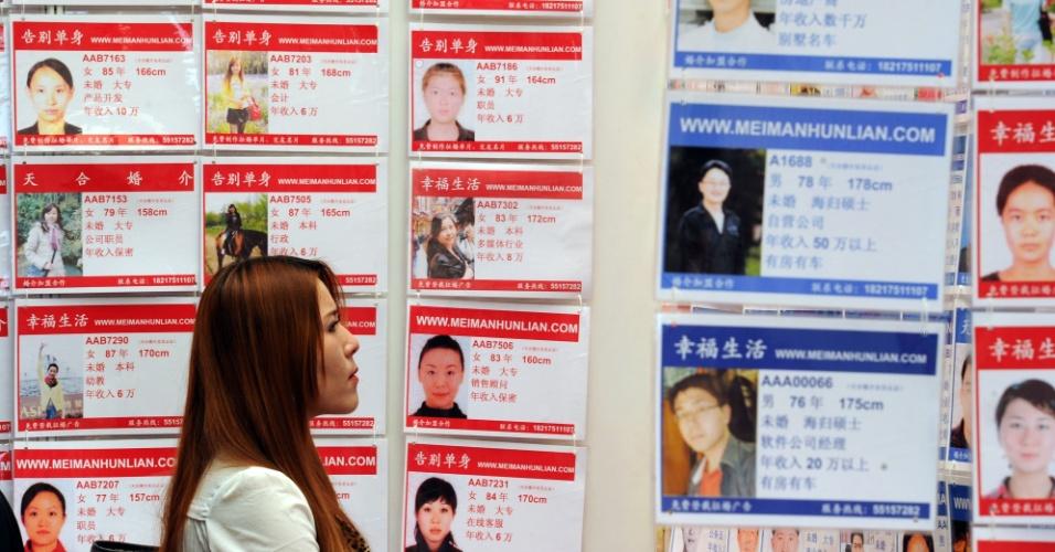 27.mai.2012 - Uma mulher olha cartazes de possíveis pretendentes numa agência de encontros, durante a Feira de Casamentos de Xangai, na China, neste domingo (27)