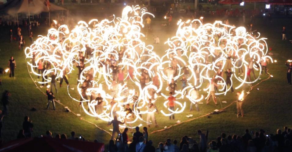 """Artistas dançam formando o desenho de um coração com tochas de fogo durante apresentação na """"Festa do Fogo"""", em Kiev, na Ucrânia"""