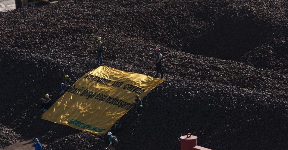 26.mai.2012 - Ativistas do Greenpeace ocupam guindastes e estendem faixa em cima de uma pilha de minério de ferro no Porto de Itaqui, em São Luiz do Maranhão (MA). Segundo a entidade, o protesto foi realizado como forma de criticar o veto apenas parcial do novo Código Florestal pelo governo