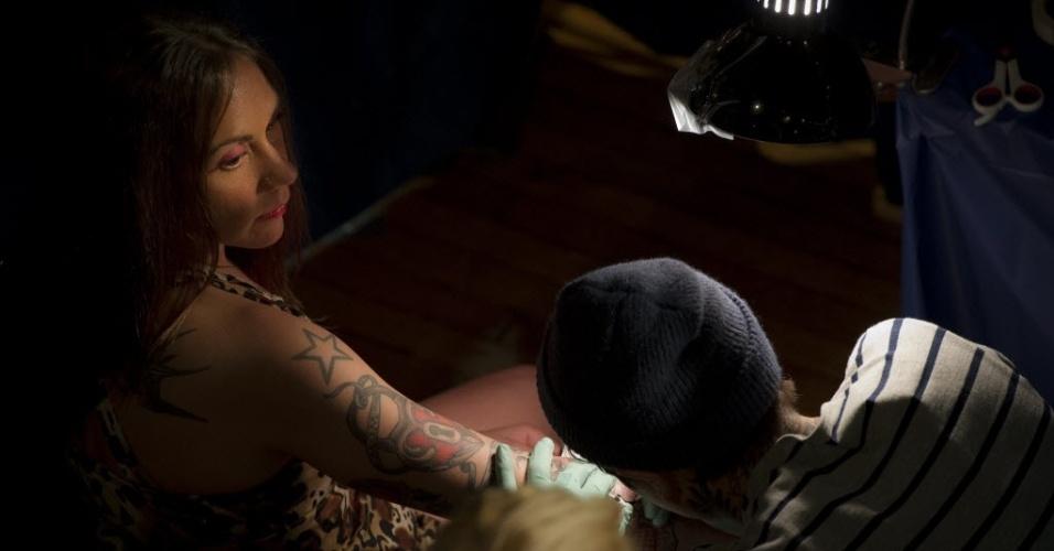 Mulheres se tatuam durante a 15ª Convenção de Tatuagem na cidade de Manhattan, em Nova York (19/5/2012)