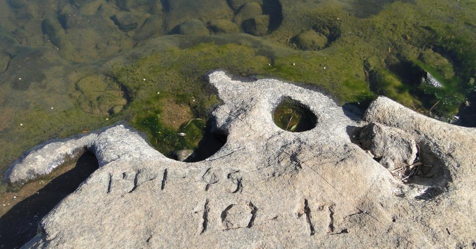 30.mai.2012 - Estiagem no Rio Grande do Sul fez com que o nível do rio Taquari, em Colina, ficasse dois metros abaixo do normal, revelando, nesta quarta-feira (30), uma pedra entalhada em 1943 por Rodolfo Binicker, em 11 de maio daquele ano, época em que a região era assolada por uma seca histórica. O entalhe foi avistado pela primeira vez em 2005
