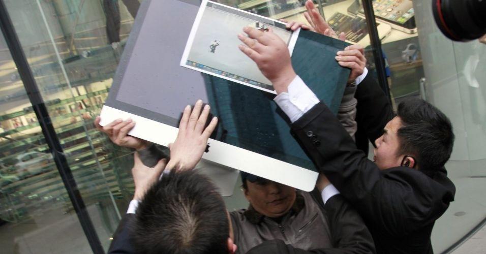 15.mar.2012 - Seguranças tentam impedir que Zou Hongqing (centro), cliente descontente com o atendimento ao consumidor da Apple, jogue seu próprio iMac no chão em protesto contra a empresa em frente à uma loja da marca em Xangai, na China. Segundo o ''China Daily'', Hongqing é dono de um iMac de 27 polegadas; ele alega que a tela do computador está desfocada depois de ser contaminada por poeira. ''O pó entrou, de alguma forma, dentro da tela. E não tem como tirar de lá porque não posso remover o vidro'', disse ao jornal. Ao contatar a Apple, Hongqing foi informado que a garantia não cobria danos causados por poeira e que ele deveria arcar com os gastos do conserto do iMac. A empresa teria dito ao cliente que o problema ocorreu devido à poluição na cidade e não a um erro no design da tela