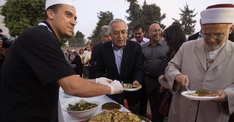 26.mai.2012 - Chefe de cozinha serve o primeiro-ministro da Palestina,  Salam Fayad, e o presidente do Conselho de Ensino Islâmico, Ekremah Sabri, durante banquete palestino de 202 metros, em Jerusalém, que ganhou o recorde mundial do Guinness