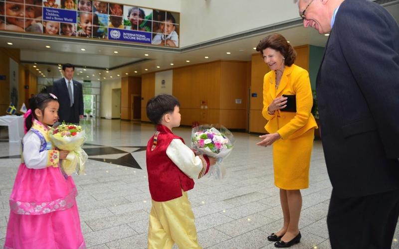 31.mai.2012 - A rainha Sílvia da Suécia recebe flores das mãos de crianças, nesta quinta-feira (31), durante visita ao Instituto Internacional de VacInas, na Universidade Nacional de Seul, na Coreia do Sul. Ao seu lado está o diretor do instituto, Christian Loucq