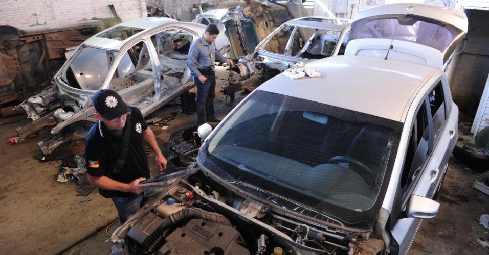 31.mai.2012 - Agentes da Polícia Civil examinam cerca de 15 veículos de luxo roubados e em processo de desmanche que foram encontrados  em uma casa no bairro Formosa, em Porto Alegre (RS). Uma pessoa foi presa