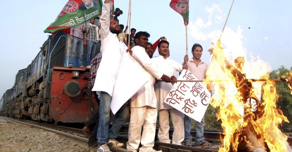 31.mai.2012 - Ativistas do Partido Samajwadi queimam boneco que representa o primeiro-ministro indiano, Manmohan Singh, após parar um trem em protesto contra o aumento do preço do petróleo em Allahabad, na Índia