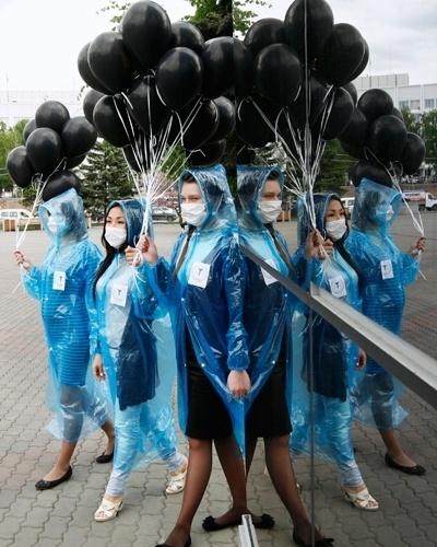 31.mai.2012 - Ativistas usam máscaras e carregam bexigas pretas durante flash mob contra cigarro na Rússia. As participantes pedem aos pedestres que não fumem. O evento faz parte da campanha do Dia Mundial sem Tabaco