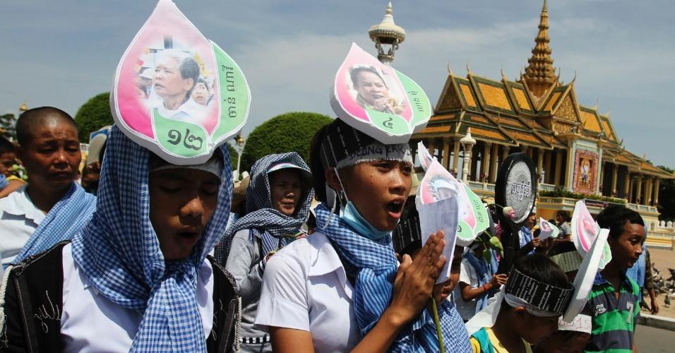 31.mai.2012 - Filhos de mulheres presas durante desocupação forçada no lago Boeung Kak (Camboja) protestam com fotografias coladas à cabeça em frente ao Palácio Real em Phnom Penh