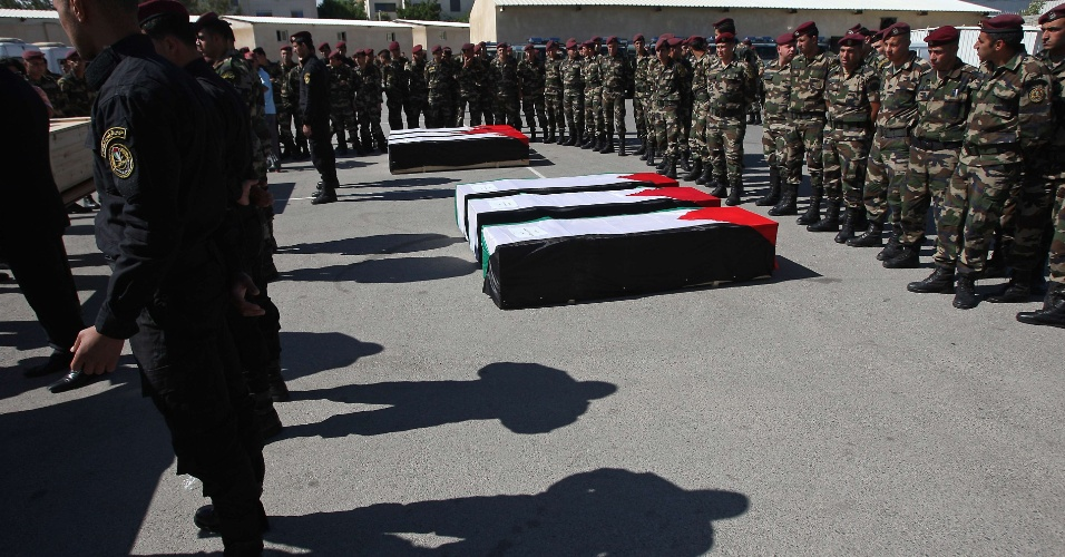 31.mai.2012 - Forças de segurança palestinas observam caixões cobertos com bandeiras antes de funeral de 91 palestinos cujos restos mortais foram devolvidos por Israel em Ramallah, na Cisjordânia