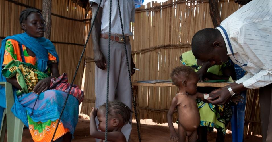 31.mai.2012 - Funcionário de agência humanitária examina criança em Yida, no Sudão, nesta quinta-feira (31). O local se tornou um porto seguro para os refugiados, que fogem dos combates entre as forças rebeldes do Exército de Libertação do Sudão e o exército regular do país