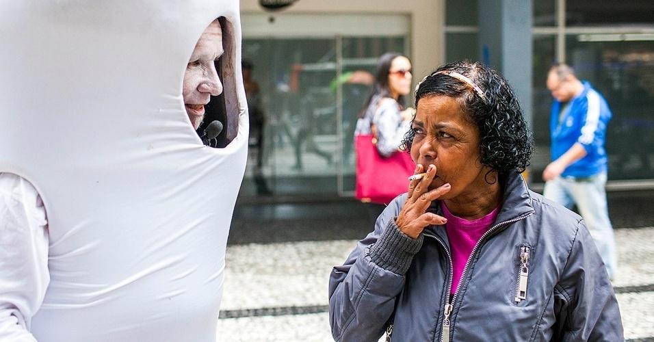 31.mai.2012 - Homem-Bituca convence fumante a larga o cigarro na avenida Paulista, em São Paulo. A iniciativa do hospital A.C.Camargo marca o Dia Mundial sem Tabaco e foi feita para difundir informações sobre o quanto o cigarro está relacionado a doenças cardiorrespiratórias, dezena de tipos de câncer, além dos benefícios de se parar de fumar