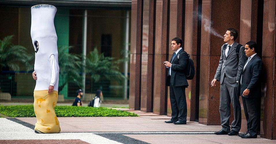 31.mai.2012 - Homem-Bituca observa fumantes na avenida Paulista, em São Paulo. A iniciativa do hospital A.C.Camargo marca o Dia Mundial sem Tabaco e foi feita para difundir informações sobre o quanto o cigarro está relacionado a doenças cardiorrespiratórias, dezena de tipos de câncer, além dos benefícios de se parar de fumar