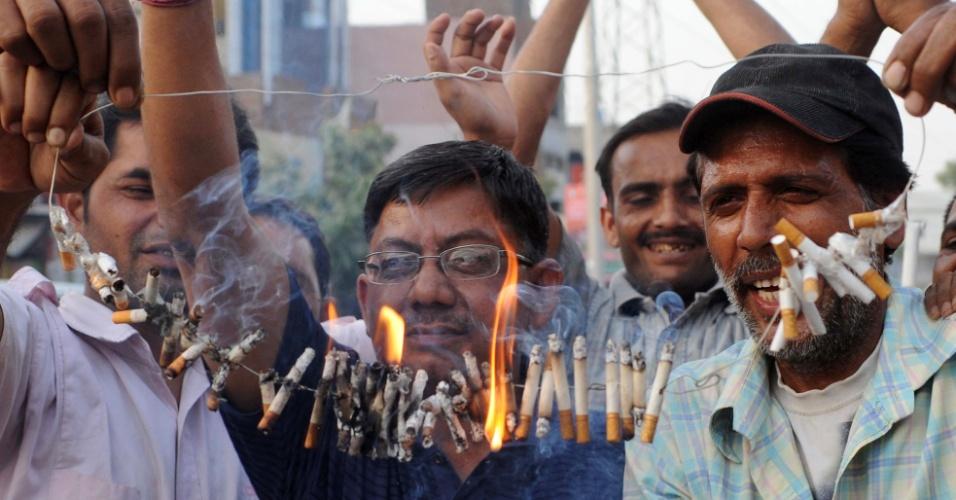 31.mai.2012 - Indianos queimam cigarros em Amritsar, nesta quinta-feira (31), celebrando o Dia Mundial sem Tabaco