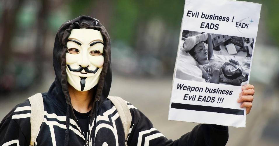 31.mai.2012 - Manifestante usando máscara protesta em frente ao hotel Okura, durante encontro anual do Eads (Companhia Europeia Espacial e de Defesa Aeronáutica), em Amsterdã, na Holanda