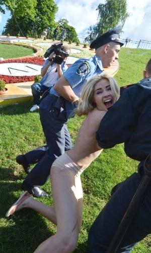 31.mai.2012 - Policiais detêm feministas do grupo Femen durante protesto das ativistas em frente à escultura de flores que representa os mascotes do euro, na praça da Independência, em Kiev, capital da Ucrânia