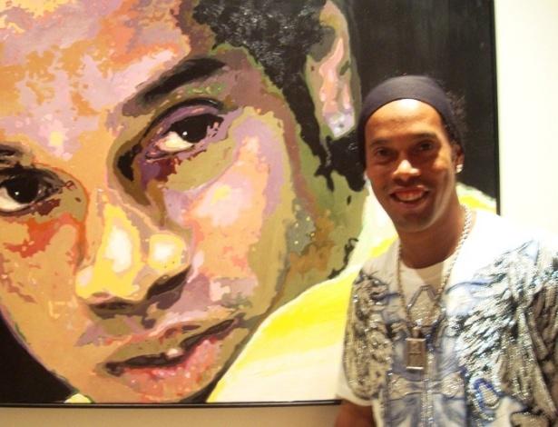 Ronaldinho Gaúcho posa em frente a um autorretrato na sua casa (31/05/2012)