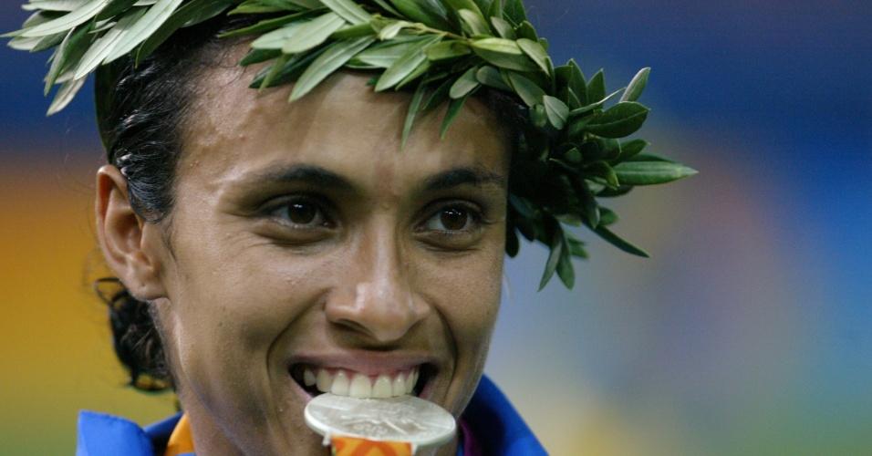 Marta morde a medalha de prata conquistada no futebol nos Jogos Olímpicos de Atenas-2004