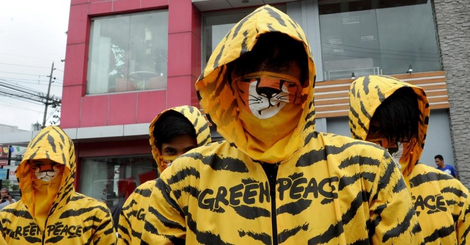 2.jun.2-12 - Fantasiados de tigres, ativistas do Greenpeace protestam na frente da lanchonete KFC (Kentucky Fried Chicken), em Manila, nas Filipinas, contra o desmatamento