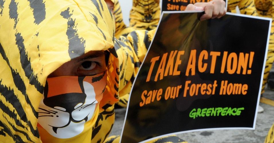 2.mai.2012 - Ativista do Greenpeace exibe cartaz e pede que a lanchonete KFC (Kentucky Fried Chicken) não contribua com o desmatamento na Indonésia, habitat natural do tigre-de-sumatra, durante protesto realizado em Manila, nas Filipinas