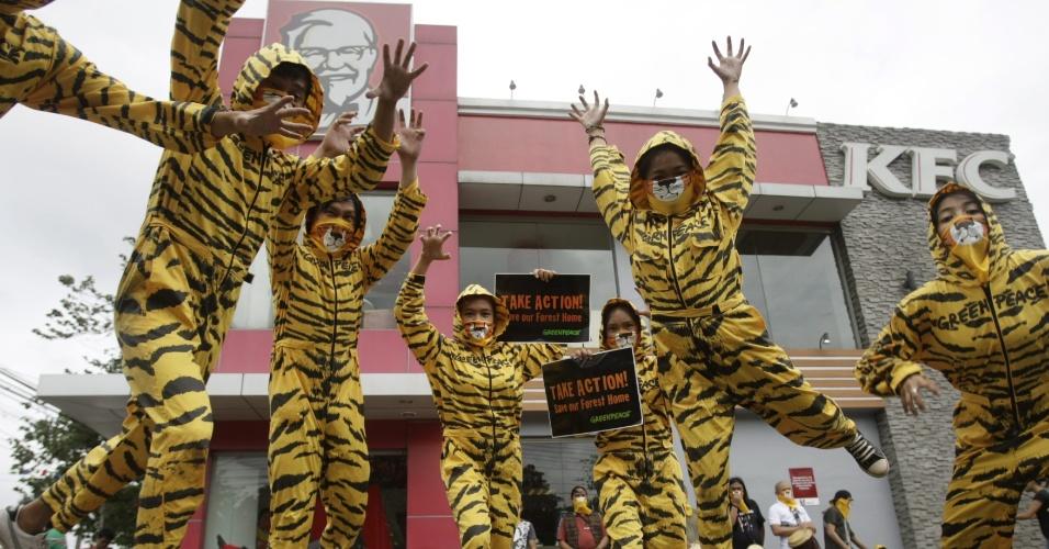 2.mai.2012 - Ativistas do Greenpeace se vestem de tigre durante protesto realizado na frente da lanchonete KFC (Kentucky Fried Chicken), em Manila, nas Filipinas, contra o desmatamento.