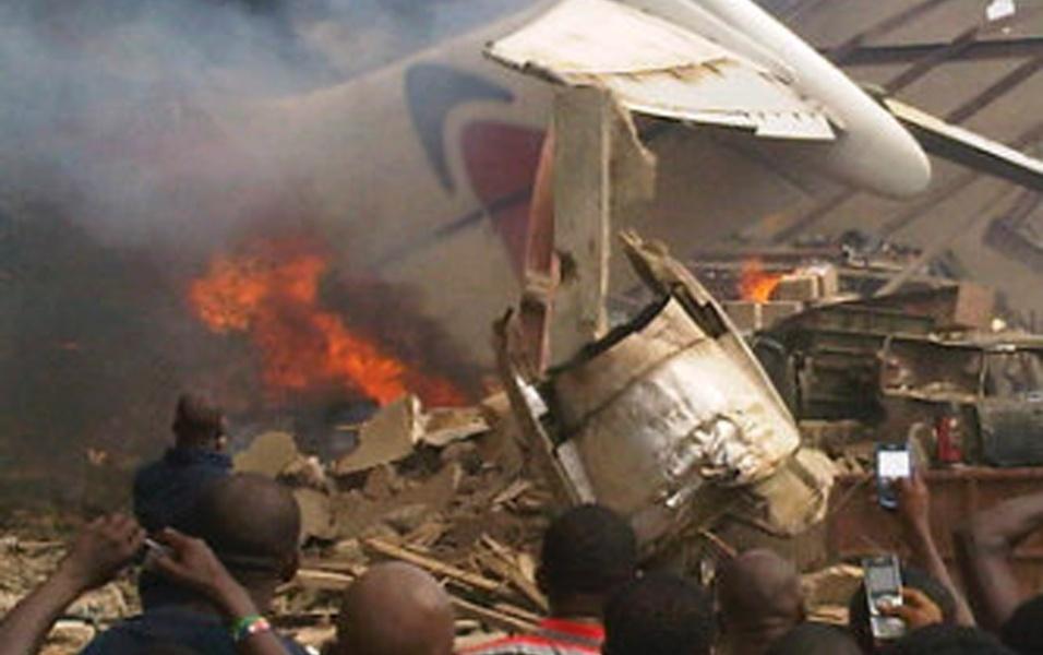 3.jun.2012 - Destroços do avião que caiu neste domingo em um bairro de Lagos, capital econômica da Nigéria, após bater em um prédio.  A aeronave levava 153 pessoas a bordo