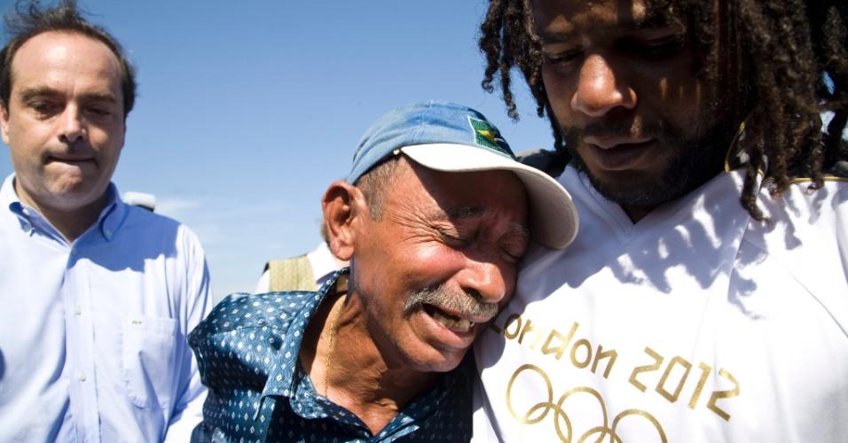 3.jun.2012 -  Homem conforta o catador de lixo Brizolla, que trabalhava no lixão de Gramacho, desativado em definitivo neste domingo