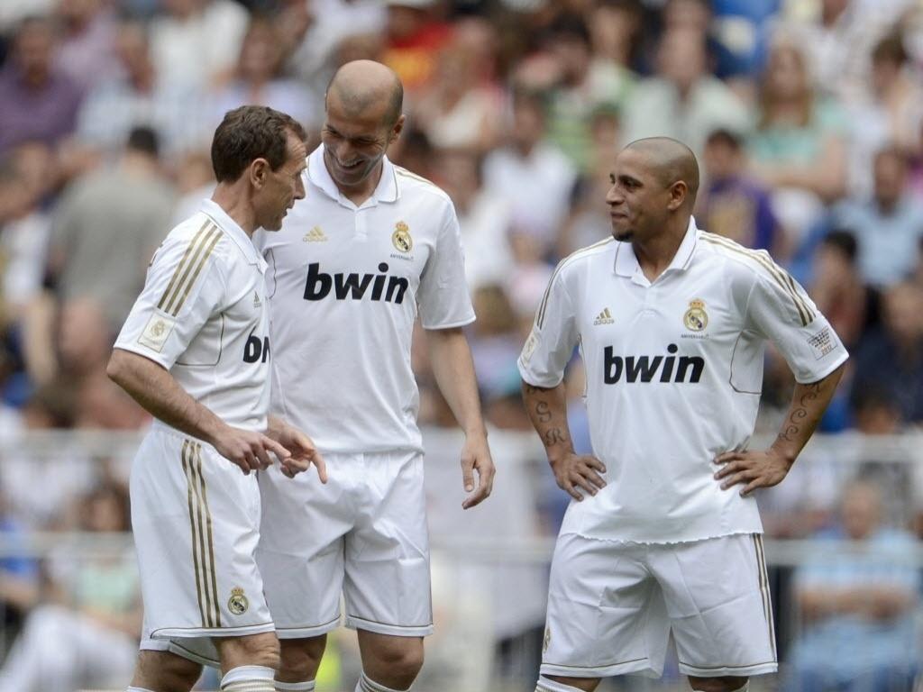 Emilio Butragueno, Zinedine Zidane e Roberto Carlos, todos ex-jogadores do Real, conversam durante amistoso contra o Manchester United
