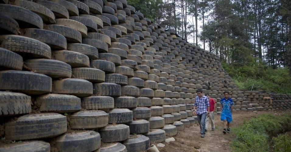 04.jun.2012 - Crianças caminham ao longo de um muro construído com pneus por membros da organização ?Long Way Home?, que promove o uso de materiais recicláveis na construção civil, em San Juan Comalapa, a 82 quilômetros da Cidade da Guatemala, na Guatemala