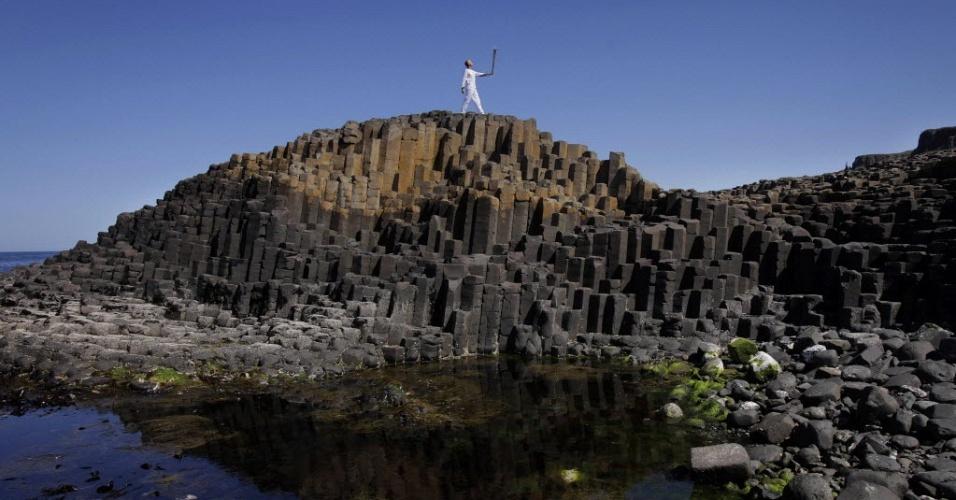 4.jun.2012 - Carregador da tocha olímpica Peter Jack percorre região conhecida como Calçada dos Gigantes, em Bushmills, no norte da Irlanda