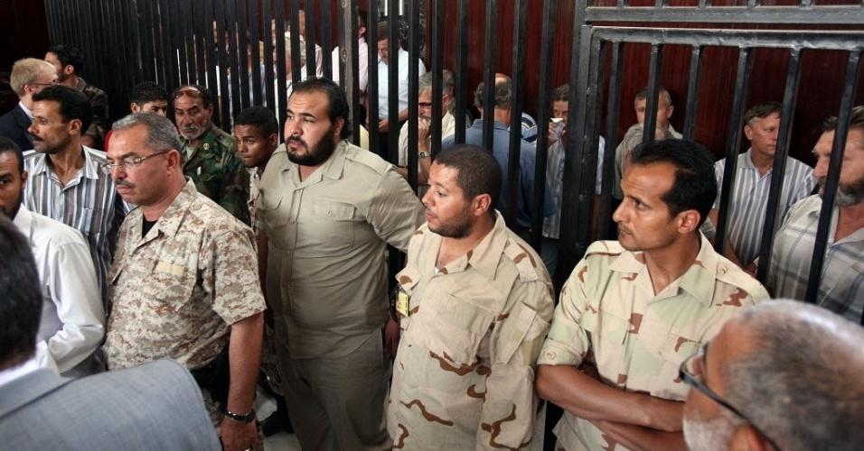 4.jun.2012 - Europeus acusados de servirem como mercenários a serviço do ditador deposto da Líbia, Muammar Gaddafi, participam atrás das grades de seu julgamento em Trípoli, capital do país. Os 24 acusados negam que trabalhassem para o ditador