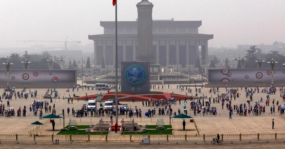 4.jun.2012 - Homem pedala na frente de multidão na Praça Tiananmen, em Pequim, na China