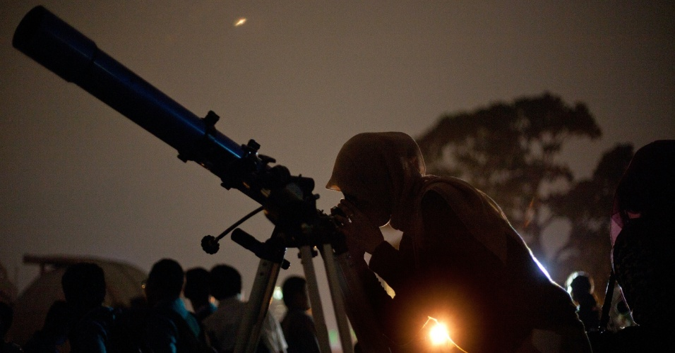 4.jun.2012 - Mulher olha em telescópio eclipse lunar parcial em Jacarta, na Indonésia