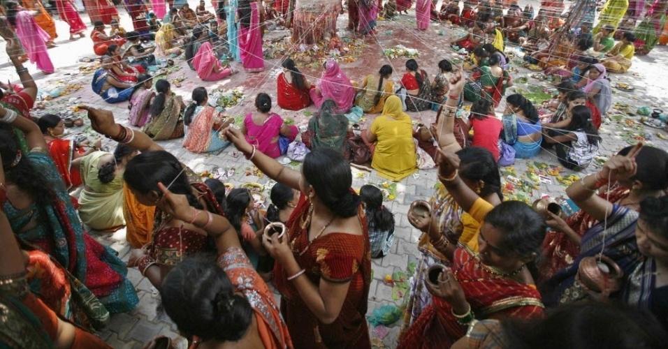 4.jun.2012 - Mulheres casadas enlaçam fios em volta de árvore banyan (considerada realizadora de desejos), em cerimônia destinada a trazer sorte, durante o festival hindu religiosa de Vata Savitri Purnima, na cidade de Ahmedabad, na Índia