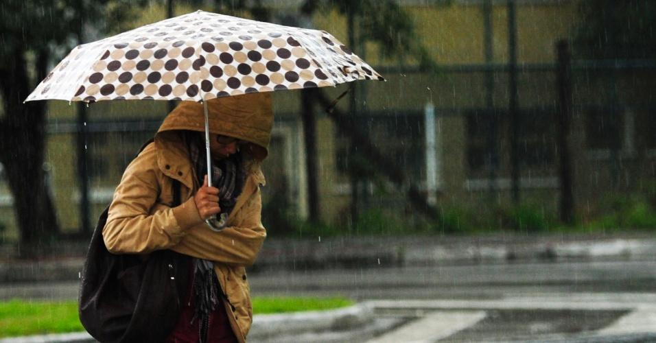 4.jun.2012 - Transeunte se agasalha para se proteger do frio e da chuva que atingiram Florianópolis nesta segunda-feira (4). Uma chuva constante cai desde domingo em várias cidades de Santa Catarina
