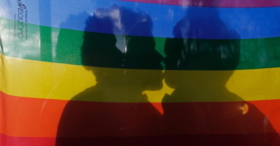 Casal gay coberto por bandeira se beija durante manifestação no Dia Internacional Contra a Homofobia, em Quito, Equador